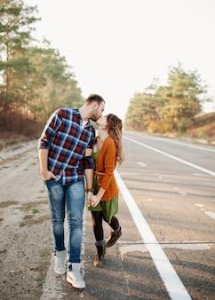 Jovem casal de homem e mulher beijando, caminhando ao ar livre em uma estrada vazia.