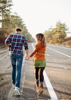 Jovem casal de homem e mulher correndo ao ar livre, de mãos dadas, em uma estrada vazia.
