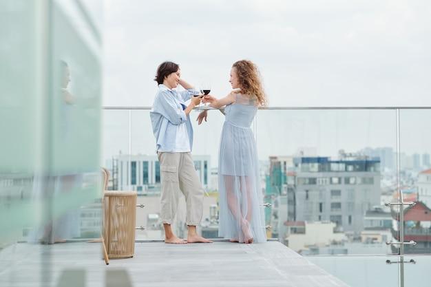 Jovem casal de lésbicas apaixonadas em pé no telhado, bebendo vinho e conversando