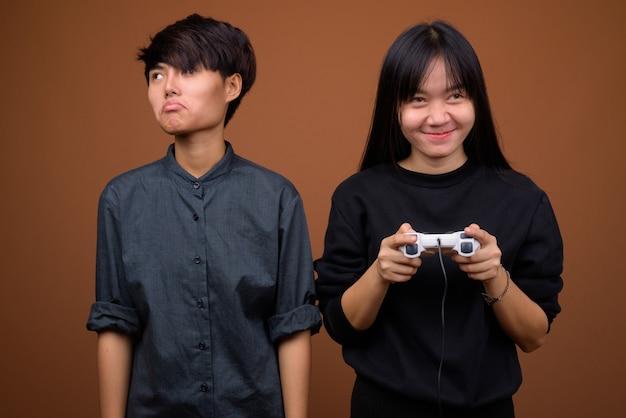 Jovem casal de lésbicas asiáticas juntas e apaixonadas contra marrom