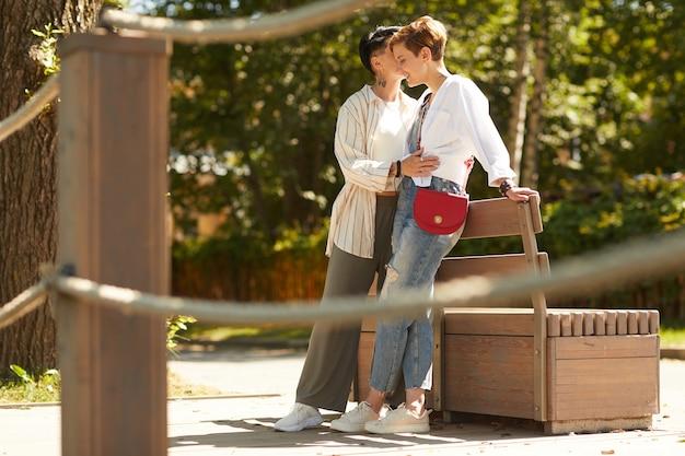 Jovem casal de lésbicas feliz se abraçando e tendo um encontro romântico no parque