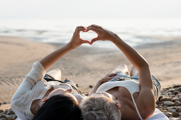 Jovem casal de lésbicas formando coração com a mão