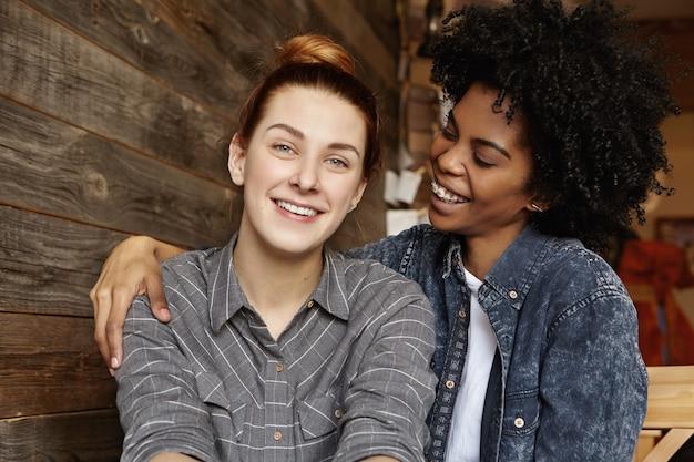 Jovem casal de lésbicas inter-raciais elegantes curtindo o tempo juntos, se abraçando e acariciando