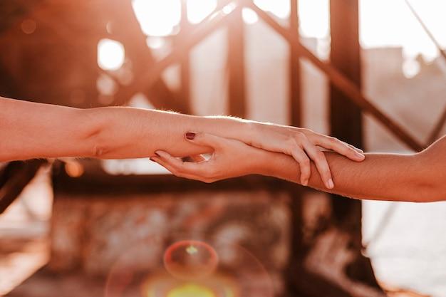 Jovem casal de lésbicas irreconhecíveis, de mãos dadas ao pôr do sol ao ar livre