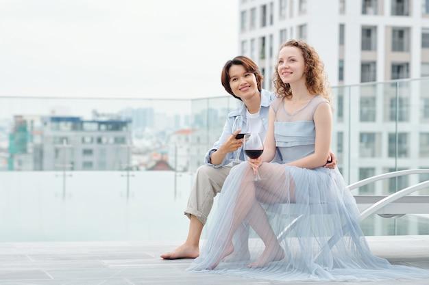 Jovem casal de lésbicas multiétnico sonhador bebendo vinho e sonhando com o futuro