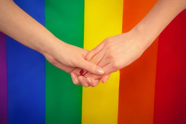Jovem casal de lésbicas na bandeira lgtbq
