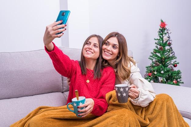 Jovem casal de lésbicas tomando café, tirando fotos e se divertindo perto da árvore de natal. conceito, relaxamento e vida familiar do casal lgbt.