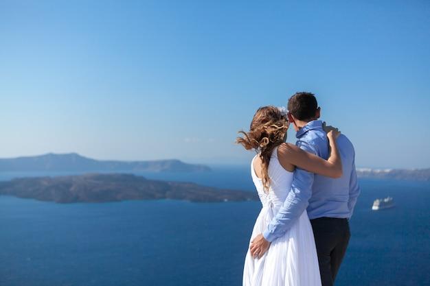 Jovem casal de lua de mel na ilha mais romântica santorini, grécia
