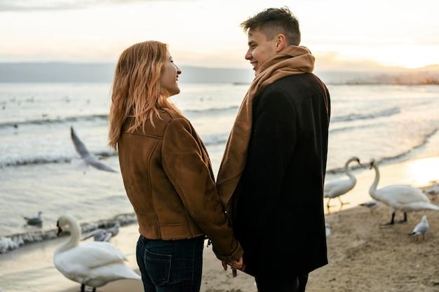 Jovem casal de mãos dadas na praia no inverno