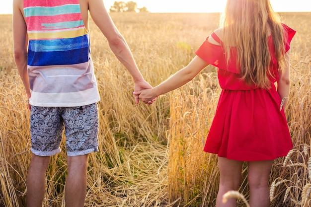 Jovem casal de mãos dadas no campo de trigo em um dia ensolarado de verão