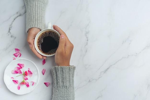 Jovem casal de mãos dadas para comer café em uma mesa de madeira.