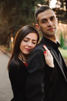 Jovem casal de mãos dadas, sorrir e passear no parque em um dia de outono.