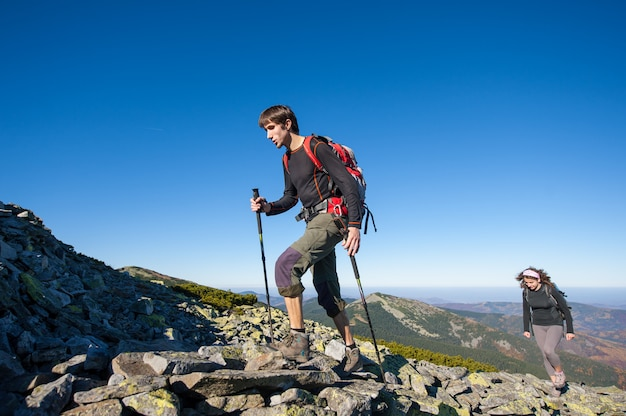 Jovem casal de mochileiros andando rochoso topo da montanha