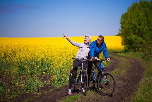 Jovem casal de motoqueiros passeando no campo de colza da primavera