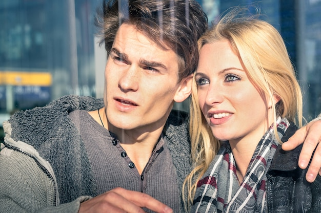 Jovem casal de namorados atrás de reflexos de vidro