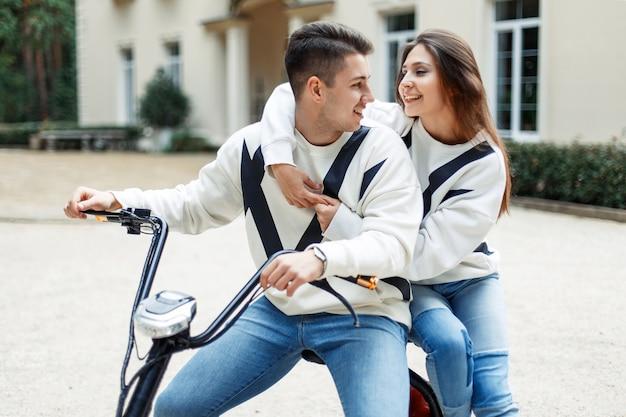 Jovem casal de namorados em roupas da moda anda de bicicleta