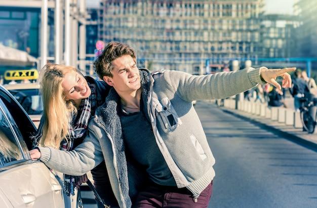 Jovem casal de namorados lidando com um táxi no centro da cidade