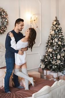 Jovem casal de namorados se abraçando na cama em um quarto ao lado de uma árvore de natal decorada