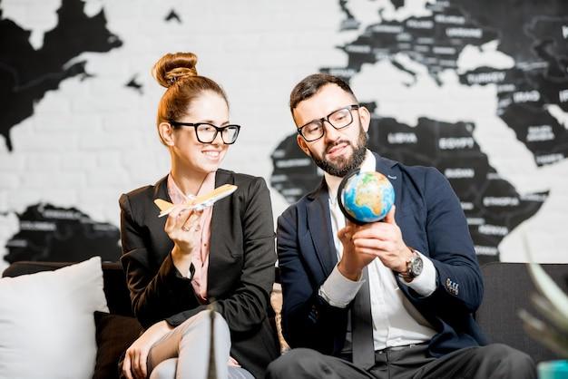 Jovem casal de negócios brincando com um globo e um avião sentado no escritório da agência de viagens com um lindo mapa-múndi ao fundo