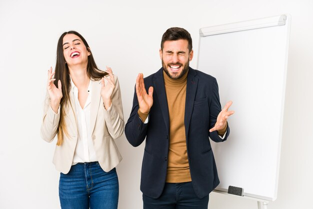 Jovem casal de negócios caucasiano isolado alegre rindo muito. conceito de felicidade.