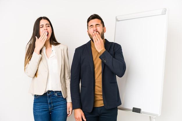 Jovem casal de negócios caucasiano isolado bocejando mostrando um gesto cansado, cobrindo a boca com a mão.