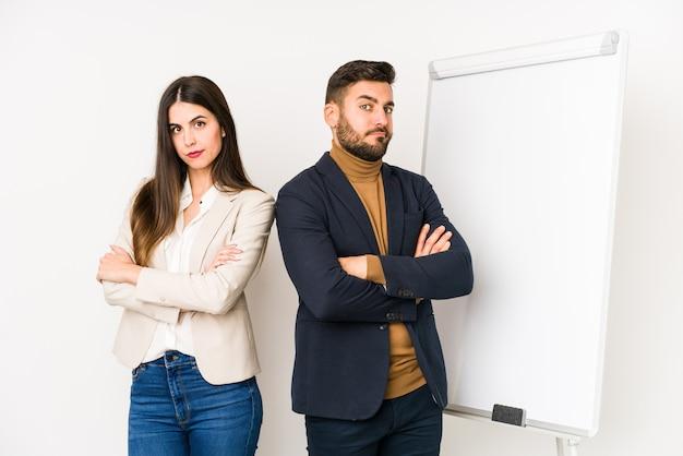 Jovem casal de negócios caucasiano isolado infeliz olhando na câmera com expressão sarcástica.