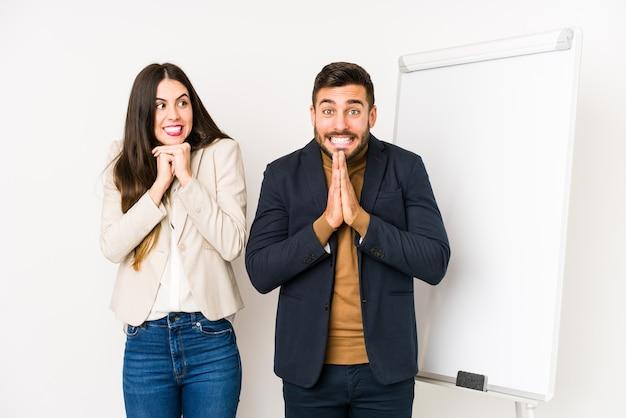Jovem casal de negócios caucasiano isolado mantém as mãos sob o queixo, olhando alegremente para o lado.