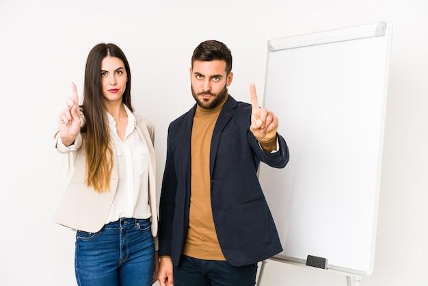 Jovem casal de negócios caucasiano isolado mostrando o número um com o dedo.