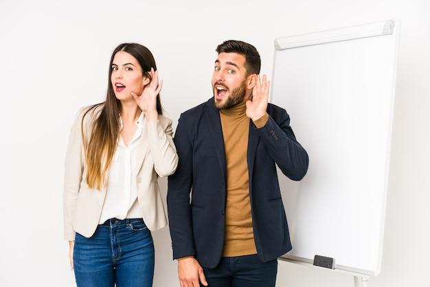 Jovem casal de negócios caucasiano isolado tentando ouvir uma fofoca.