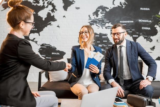 Jovem casal de negócios escolhendo uma viagem com um agente sentado no escritório da agência de viagens com um mapa-múndi ao fundo