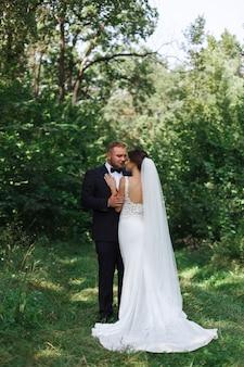 Jovem casal de noivos desfrutando de momentos românticos lá fora. abraço apaixonado de noivas de fora os noivos na caminhada ao ar livre em dia de sol. casamento . dia do casamento no parque verde
