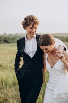 Jovem casal de noivos juntos no campo
