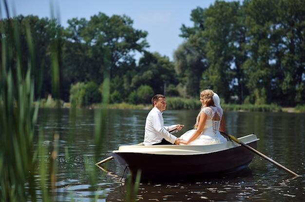 Jovem casal de noivos navegando no barco