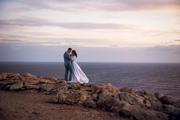 Jovem casal de noivos, noiva e noivo caminhando e se abraçando em uma praia rochosa perto do mar à noite em chipre