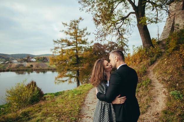 Jovem casal de noivos se abraçando e se beijando no fundo do castelo e do lago no outono