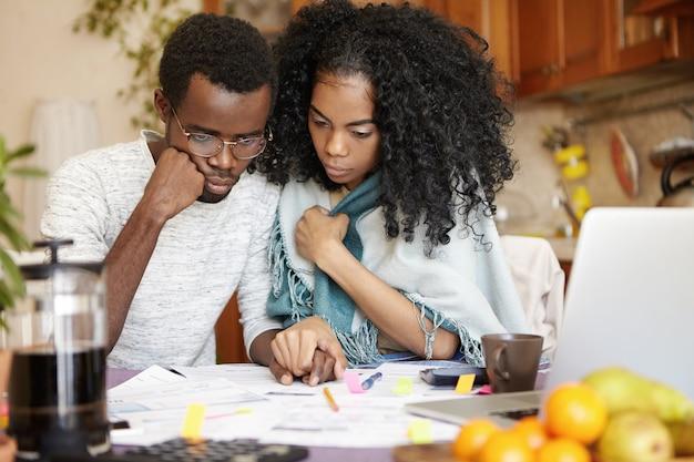 Jovem casal de pele escura gerenciando finanças, sentado à mesa da cozinha com olhares estressados