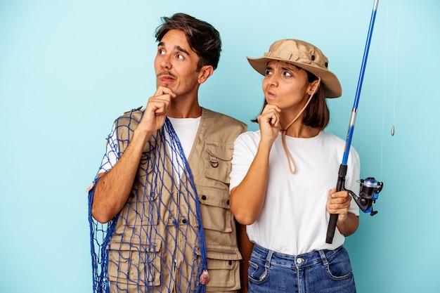 Jovem casal de pescadores de raça mista isolado em fundo azul, olhando de soslaio com expressão duvidosa e cética.