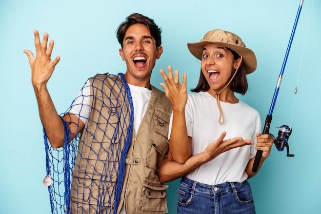 Jovem casal de pescadores de raça mista isolado em fundo azul, recebendo uma agradável surpresa, animado e levantando as mãos.