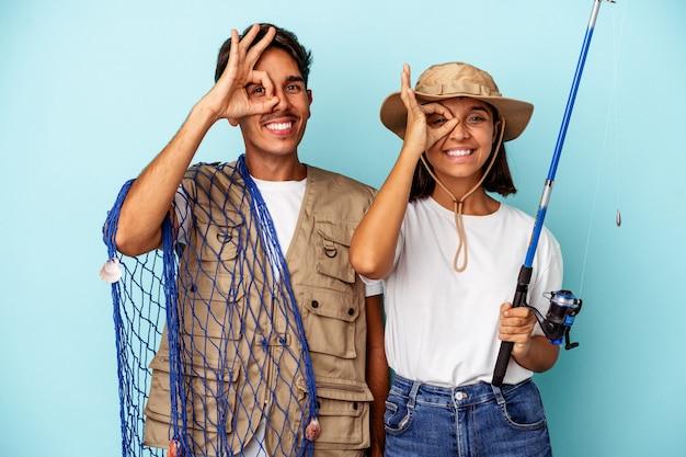 Jovem casal de pescadores de raça mista isolado em um fundo azul animado, mantendo o gesto ok no olho.