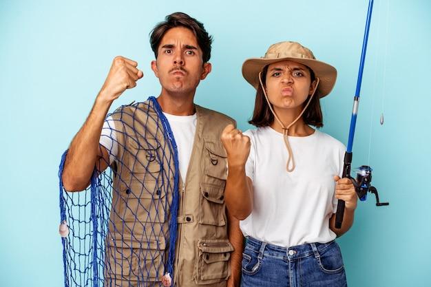 Jovem casal de pescadores de raça mista isolado em um fundo azul, mostrando o punho para a câmera, expressão facial agressiva.