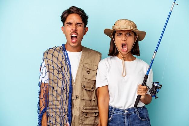Jovem casal de pescadores de raça mista isolado no fundo azul, gritando muito zangado e agressivo.