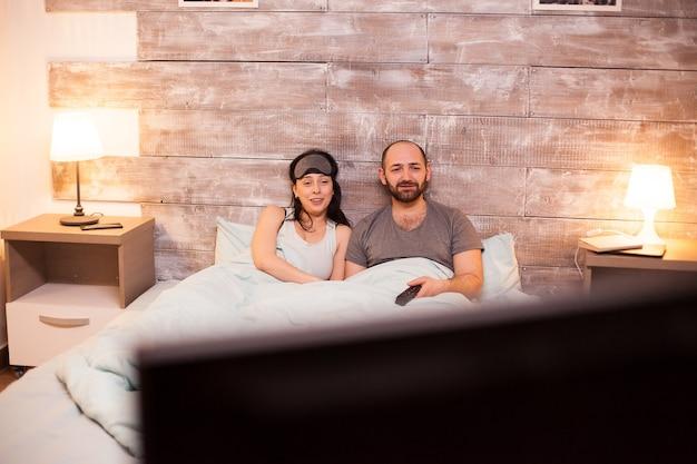 Jovem casal de pijama relaxando assistindo tv depois de um dia difícil no trabalho.