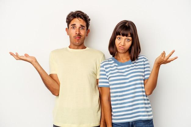 Jovem casal de raça mista isolado no fundo branco duvidando e encolhendo os ombros em gesto de questionamento.