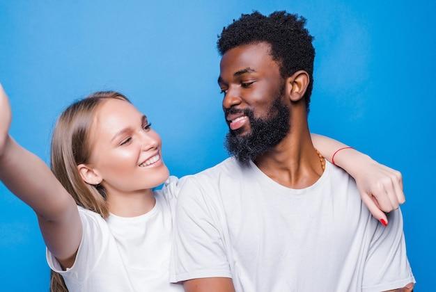 Jovem casal de raça mista tirando uma selfie isolada na parede azul