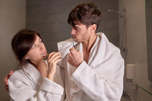 Jovem casal de roupão branco, escovando os dentes no banheiro