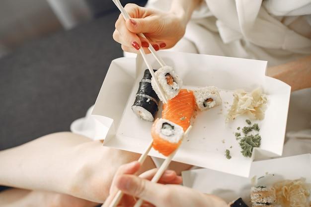 Jovem casal de roupões de banho comendo sushi.