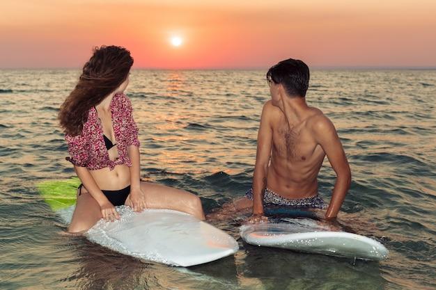 Jovem casal de surfistas