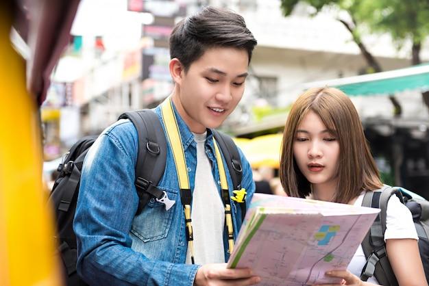 Jovem casal de turistas asiáticos mochileiros procurando direção no mapa