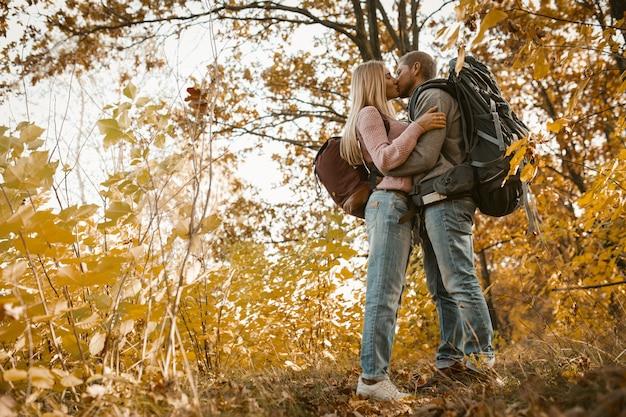 Jovem casal de turistas beijando na floresta ao ar livre