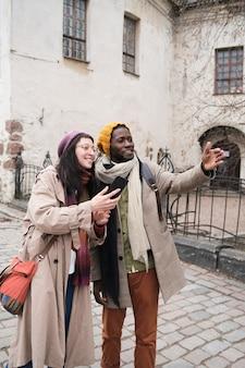Jovem casal de turistas feliz indo passear e tirando fotos ao telefone na cidade
